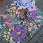 Fotografia dzieci stojących na namalowanej łące