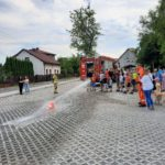 Bezpieczne wakacje - uczestnicy spotkania używają węża strażackiego