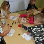 Dzieci odbijające stempelki na papierowych książeczkach