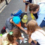 Dzieci układające puzzle podczas gry terenowej zagadkowi odkrywcy