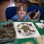 Dziewczynka tworząca mandalę z kwiatów