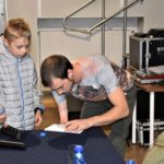 Jasiek Mela dający autograf chłopcu uczestniczącemu w spotkaniu