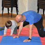 Tata wykonujący z synem ćwiczenie rozciągające