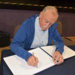Krzysztof Wielicki dokonujący wpisu do kroniki biblioteki